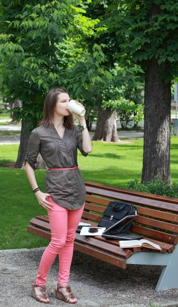 Young woman standing-up near a bench in a park and drinking a hot coffee during a break of her work on a laptop.