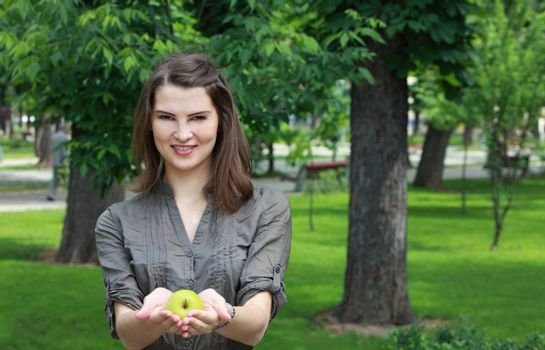 Young smiling woman offering a green apple outside in a park in summer.