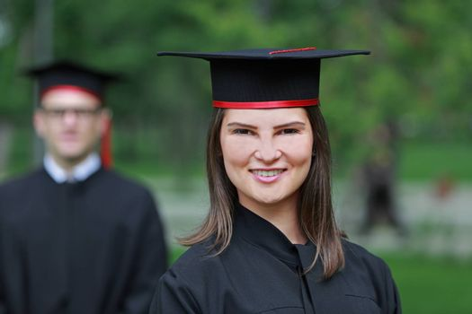 Outdoor portrait of a young student woman in the graduation day.
