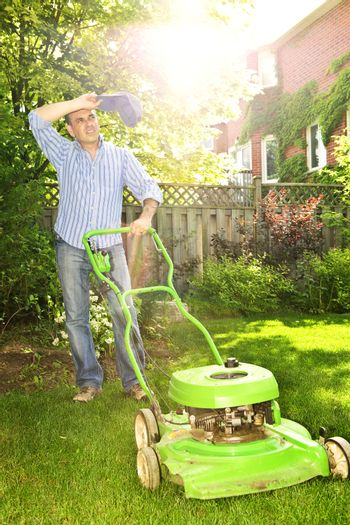 Man taking a break while mowing lawn on hot summer day