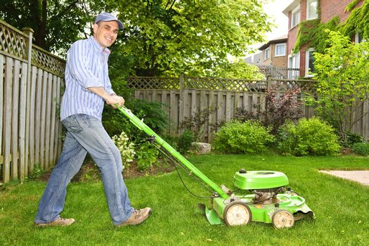 Man with lawn mower in landscaped backyard