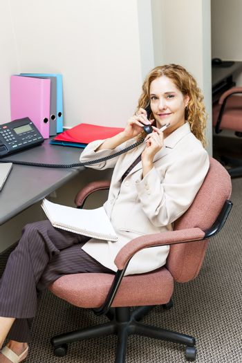 Thoughtful business woman on phone taking notes in office workstation