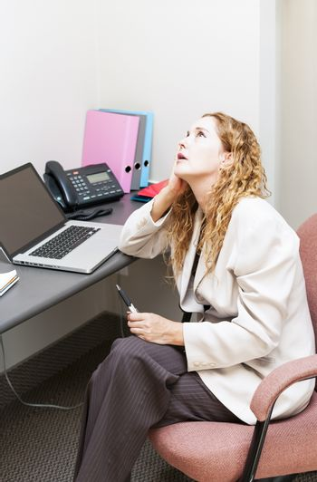 Businesswoman worried in office workstation looking up