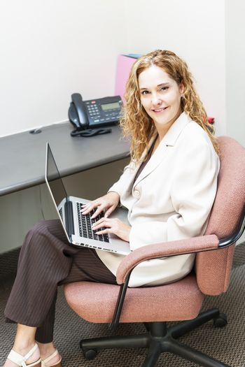 Confident businesswoman sitting at workstation in office with computer