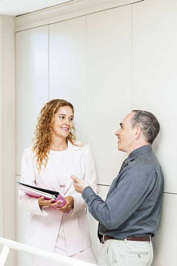 Man and woman discussing work in office hallway