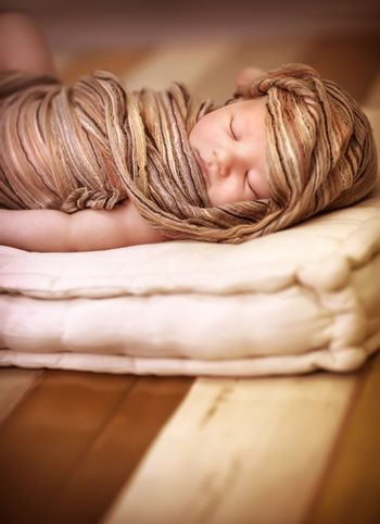 Portrait of sweet newborn baby girl sleeping, wrapped in stylish brown scarf, peaceful nap, happy childhood, kid's fashion concept