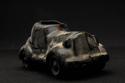 Vintage Old Ceramic Black Car on the Dark background