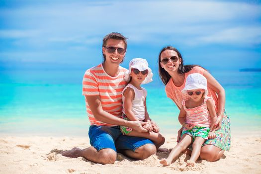 Family of four on happy beach vacation at tropical island