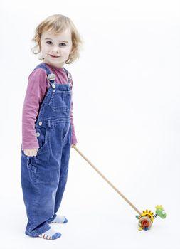 preschooler with toy standing in light background
