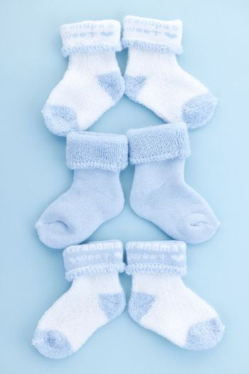 Arrangement of three pairs of blue infant boy socks for baby shower