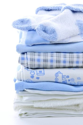 Stack of blue infant clothing for baby shower