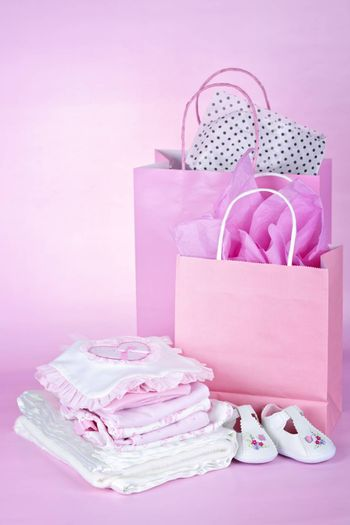 Gift bags and infant clothes for girl baby shower on pink background