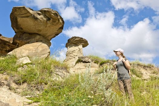 Young girl looking at hoodoos in badlands of Dinosaur provincial park, Alberta, Canada