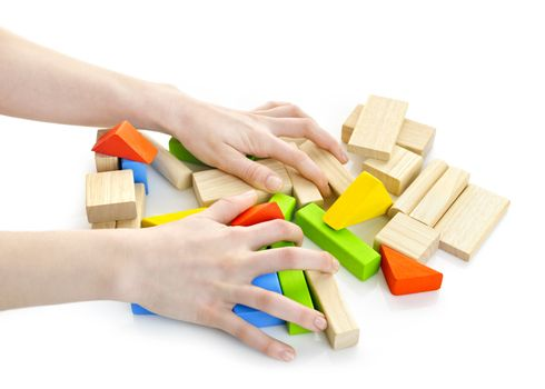 Hands with pile of wooden block toys isolated on white