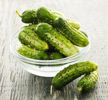 Fresh green pickling cucumbers in a glass bowl