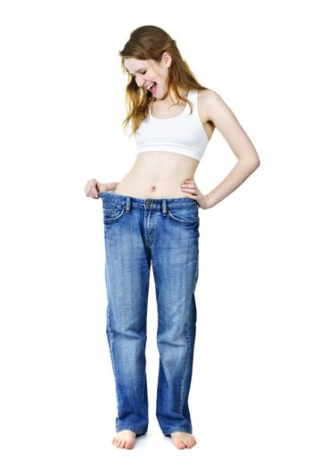 Excited fit young woman in loose old jeans after losing weight isolated on white