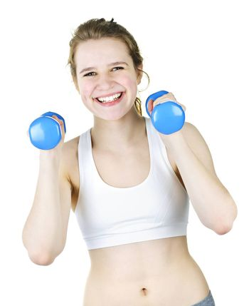 Happy smiling young woman working out with weights for fitness exercise