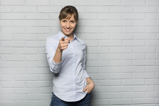 Female casual happy studio point fingers gray isolated background