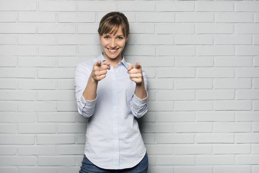 Female casual happy studio point fingers gray background
