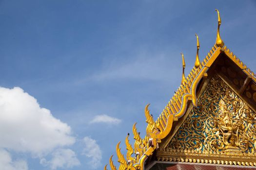 Thai temple art, beautiful roof designs. The clouds and sky.