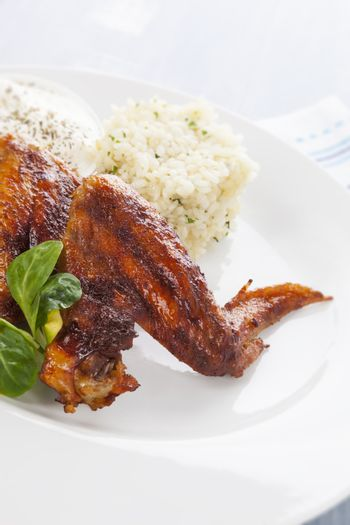 Barbeque chicken wing with rice, salad and dressing on white plate on bright background. Culinary chicken meat eating.