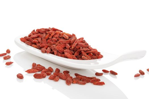 Dried goji superfood on white plate isolated on white background. Healthy superfood eating.