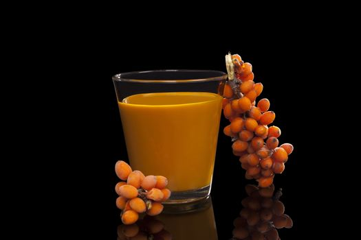 Sea buckthorn juice and berries isolated on black background. Natural detox. Healthy berry eating.