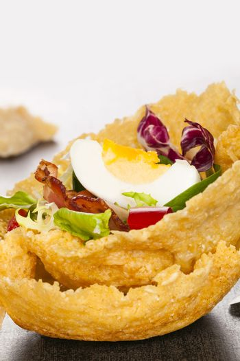 Parmigiano basket filled with fresh vegetable and bacon. Culinary cheese eating.