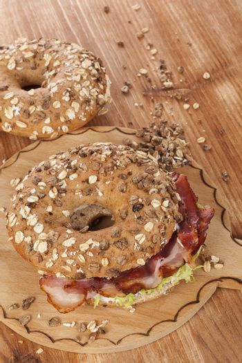 Whole grain bagel with bacon on wooden background. Culinary bagel eating.