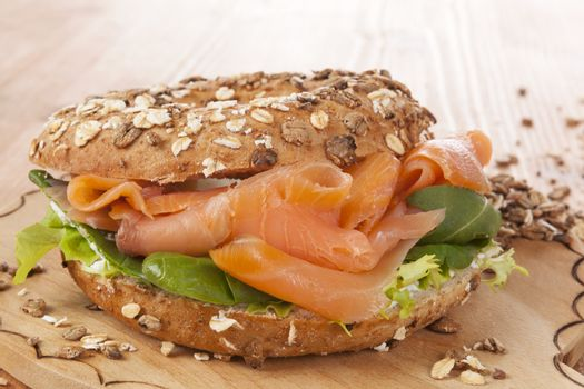 Whole grain bagel with smoked salmon on wooden background. Culinary healthy bagel eating.