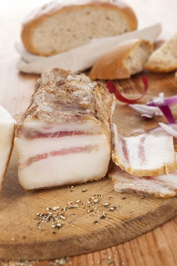 Traditional bacon background with onion and bread on wooden background, rustic style. Delicious meat eating.