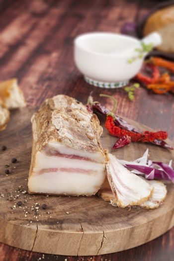 Traditional bacon eating. Big fat bacon piece, onion, herbs on wooden background. Culinary tasty meat eating.