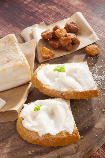 Bread slice with lard, cracklings and bacon on wooden background. Traditional culinary eating.
