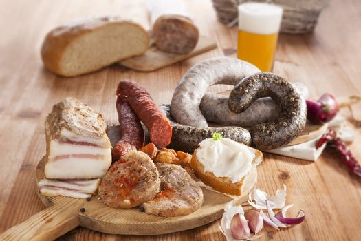 Blood sausage, rice sausage, head cheese, garlic, onion beer and bread on wooden kitchen board on wooden background. Traditional pork meat eating.