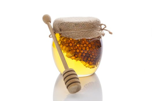Honey in glass jar with wooden dipper and honey comb isolated on white background. Organic bee honey.