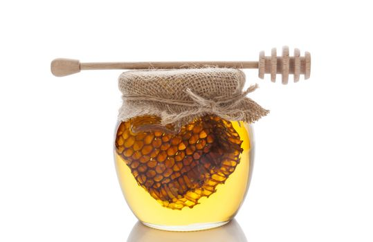 Honey in glass jar with wooden honey spoon and honey comb isolated on white background. Organic bee honey.