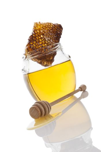 Honey in glass jar with wooden honey spoon and honey comb isolated on white background. Delicious healthy organic bee honey.