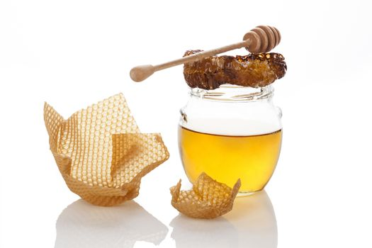 Organic honey with honey comb and wooden dipper isolated on white. Natural healthy sweetener. Alternative medicine.