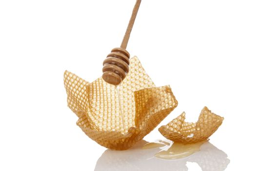 Honey dropping from wooden honey dipper onto honey comb isolated on white background. Organic honey background.