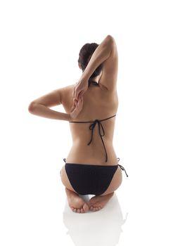 Beautiful girl kneeling and stretching backview. Yoga practice, life balance and wellness.
