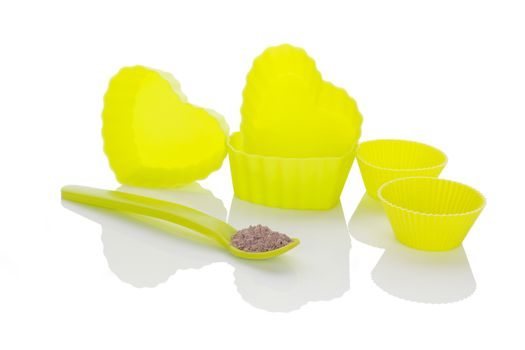 Neon hear shaped baking forms and chocolate cookie mixture isolated on white background. Baking.
