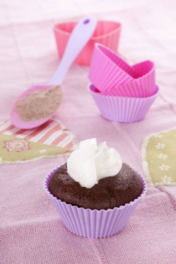 Modern contemporary baking background in purple and pink. Chocolate cupcake and baking forms with whipped cream on pink background.