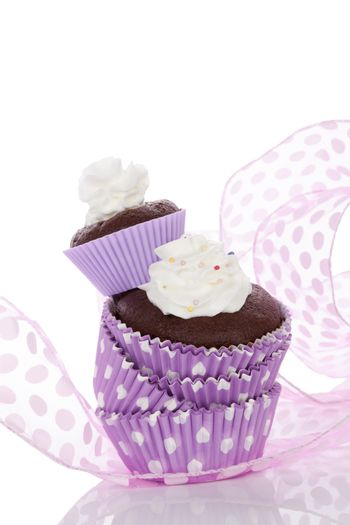 Delicious chocolate cupcake with whipped cream in purple dotted paper form isolated on white. Cupcakes baking.