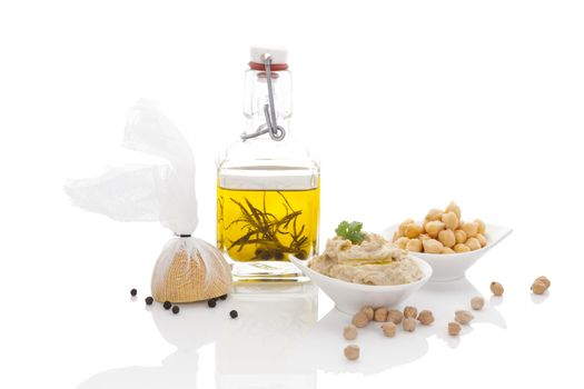 Olive oil, hummus, chickpeas and pepper corns isolated on white background. Culinary mediterranean cuisine.