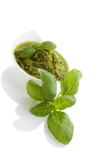 Green pesto with fresh basil herbs in white bowl isolated on white background. Culinary mediterranean eating.