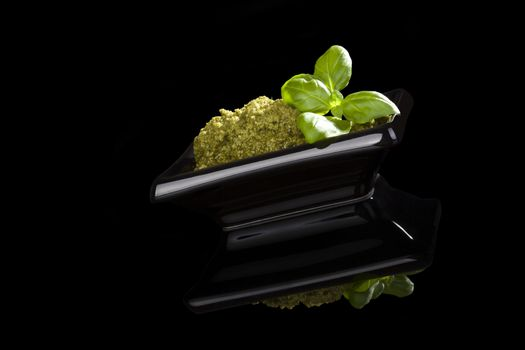 Organic green pesto with fresh basil leaves in black bowl isolated on black background. Culinary traditional pesto eating.