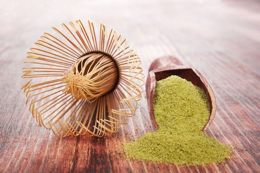 Matcha. Green powdered tea on wooden background with wooden scoop. Traditional healthy asian beverage.