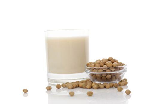 Soya milk in glass with soya beans isolated on white. Vegan milk concept.