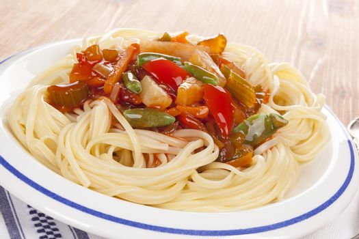 Culinary pasta with fresh vegetables on white plate. Delicious asian cuisine.