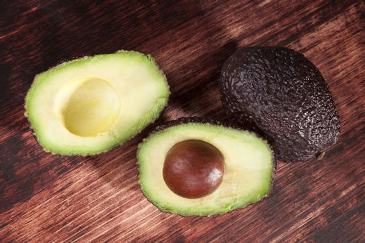 Delicious fresh ripe avocado cross section on brown wooden background, top view. Healthy fresh fruit eating.